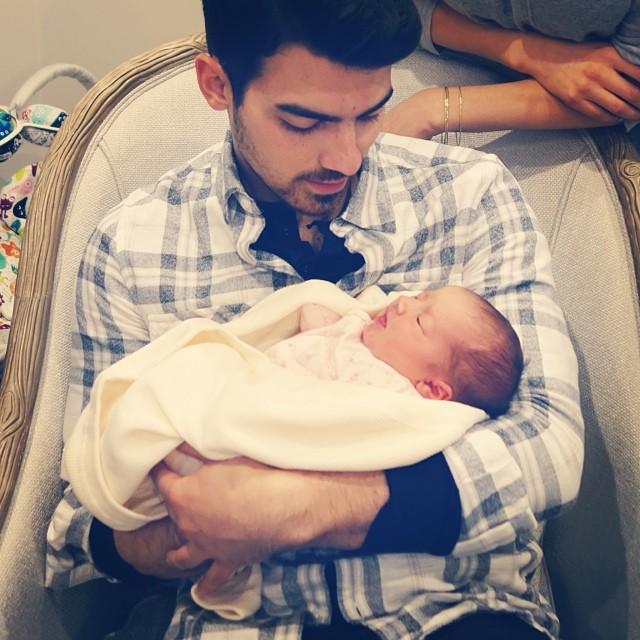 Joe Jonas cargando a su bebé en brazos y viéndolo