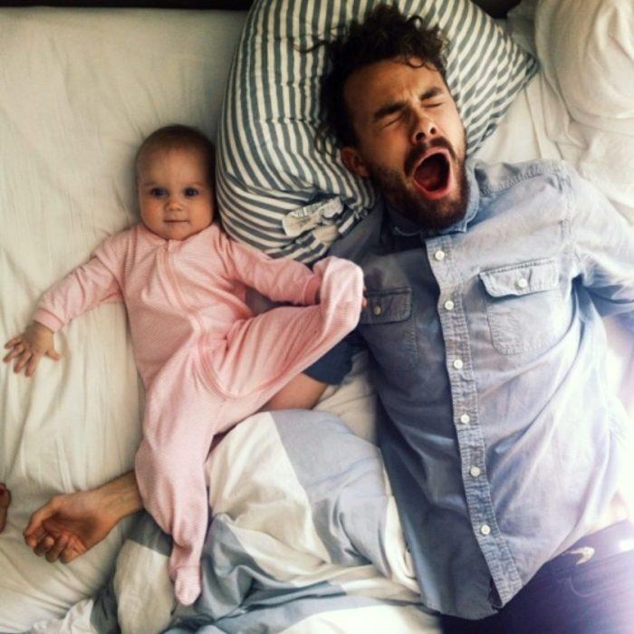 Chico bostezando mientras está recostado junto a su bebé