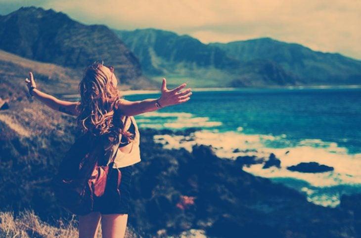 Chica con los brazos extendidos frente al mar
