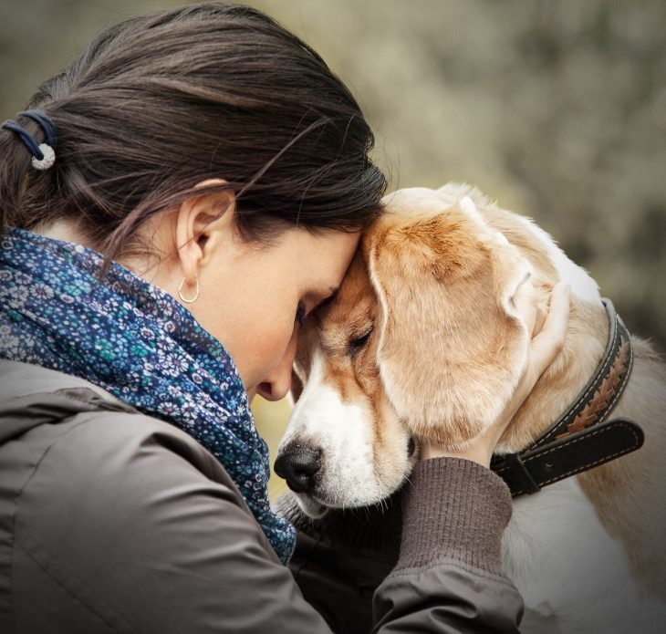 Chica abrazando a su perro mientras están en un parque