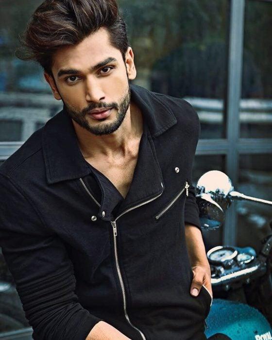 Rohit Khandelwal nuevo Mr. World usando una chaqueta negra mientras está recargado sobre una motocicleta
