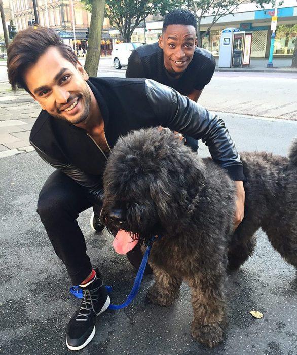 Rohit Khandelwal de la India ganador del concurso Mr. World 2016 abrazando a un perrito en color negro