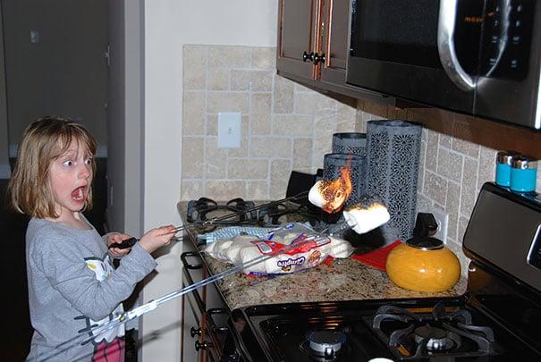 Niños asando bombones en la cocina y quemandolos