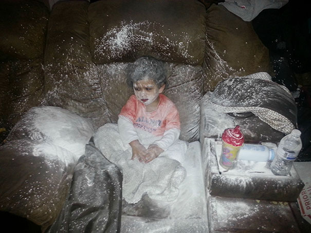 Niño travieso cubierto de harina mientras está sentado en su sofá