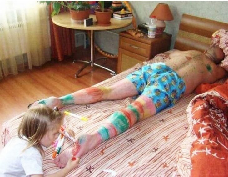 Niña dibujando a su papá mientras está recostado