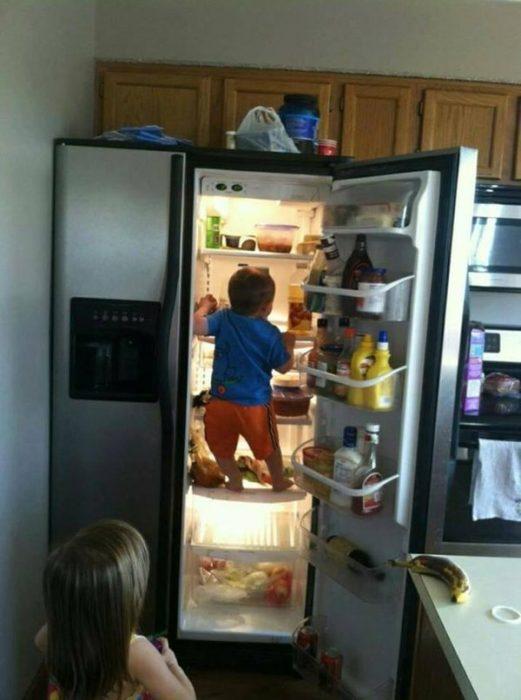 Niño escalando por el refrigerador