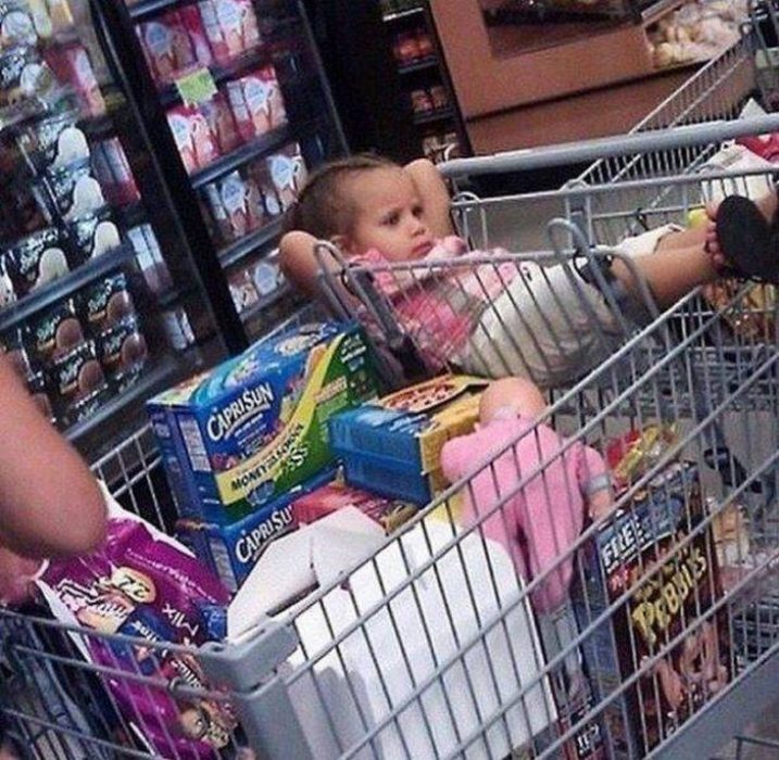Niña recostada en el carrito del supermercado