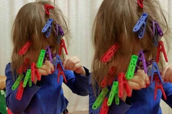 Niña con el cabello lleno de pinzas para la ropa