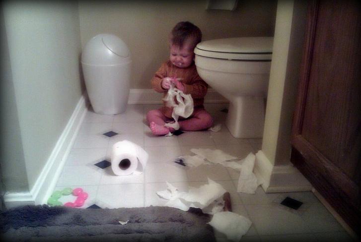 Niño comiendo papel bajo el hinodoro