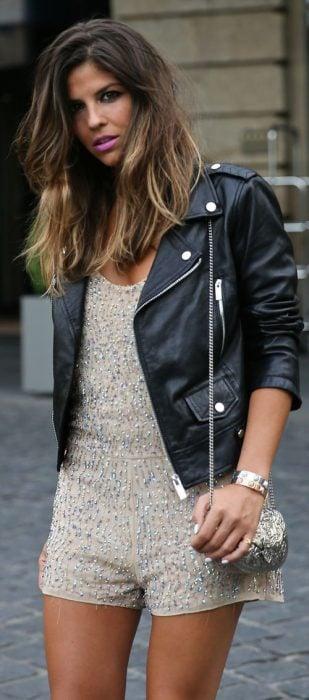 Chica usando un romper color beige con brillos y una chaqueta de cuero negra