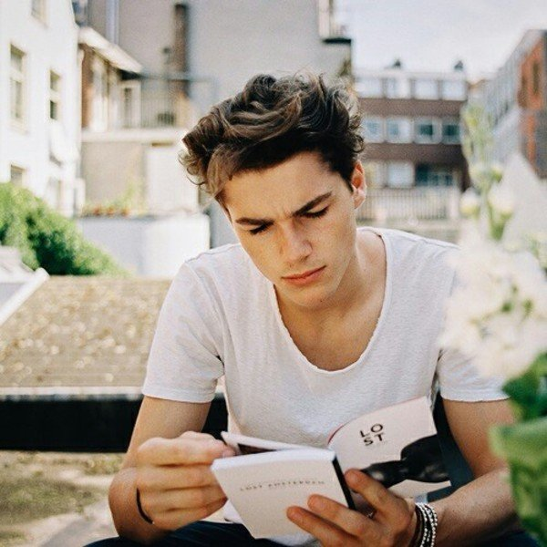Chico guapo leyendo en el parque