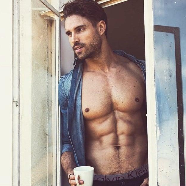 Chico con taza de café asomado por la ventana