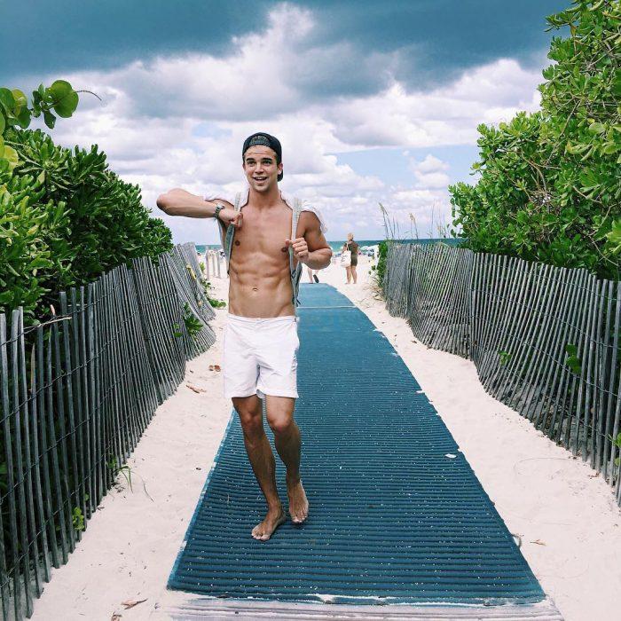 Chico sin camisa caminando por la playa
