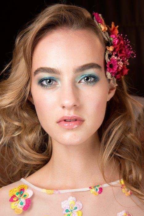 Chica usando distintas sombras en tonos azules y verdes