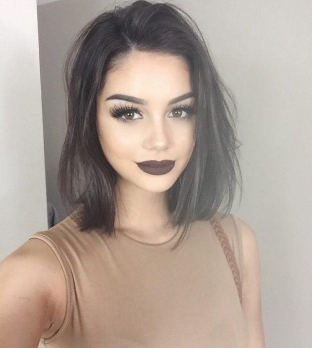 Chica usando unos labios en color café obscuro