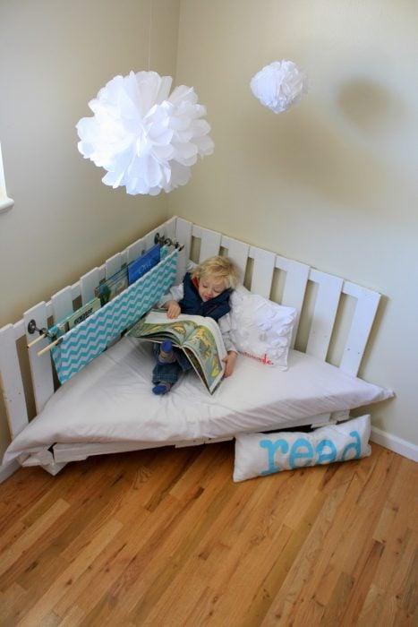 Rincón de lectura creado con palets y pintados de color blanco
