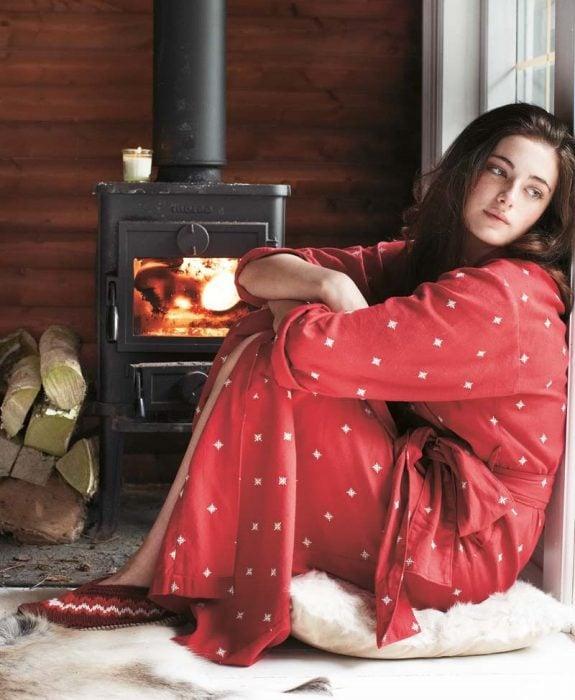 mujer con pijama roja sentada junto a la ventana pensando
