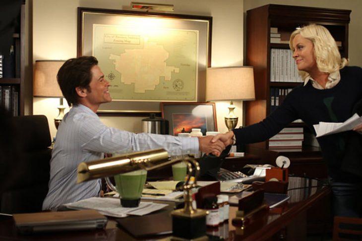 mujer rubia estrechando mano con hombre en escritorio