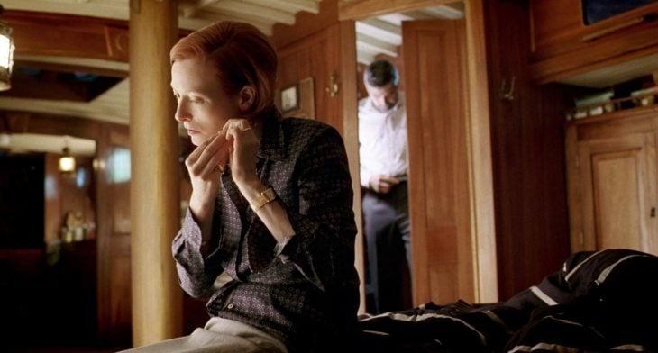 mujer pelirroja sentada poniendose arete y hombre atrás visitendóse