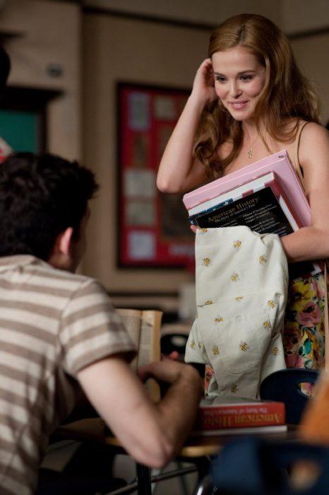 mujer rubia con libros en la mano sonriendo