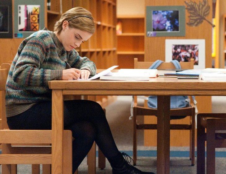 mujer rubia de cabello corto sentada estudiando