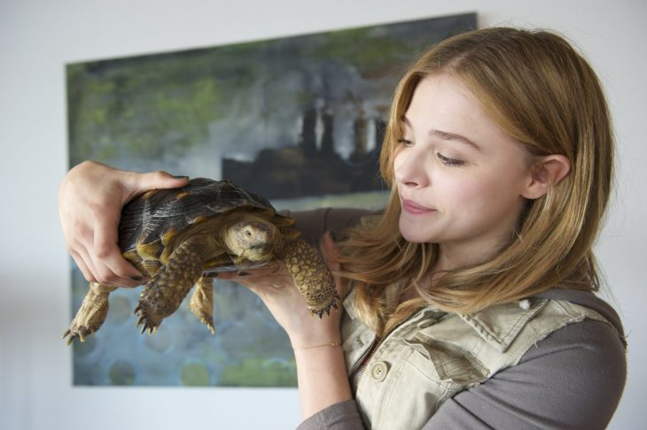 mujer rubia con tortuga en la mano