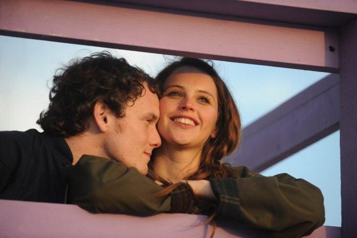hombre y mujer recargados en una ventana sonriendo