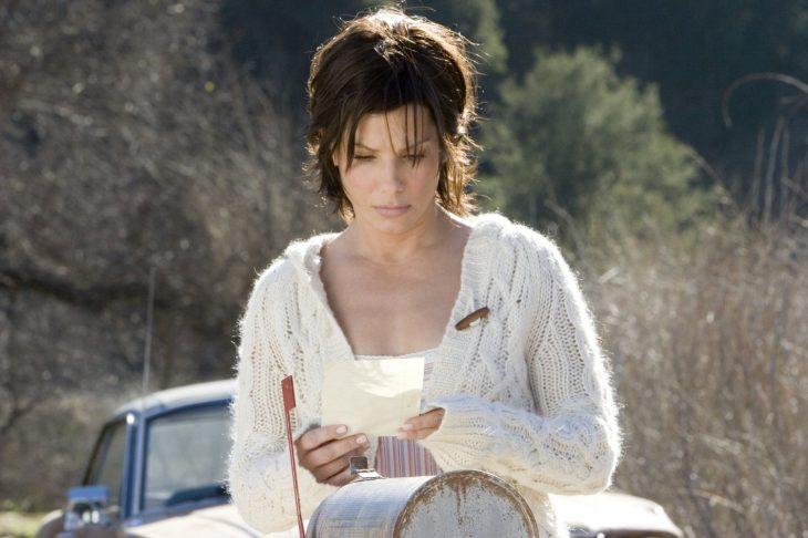 mujer cabello castaño y corto con carta en sus manos