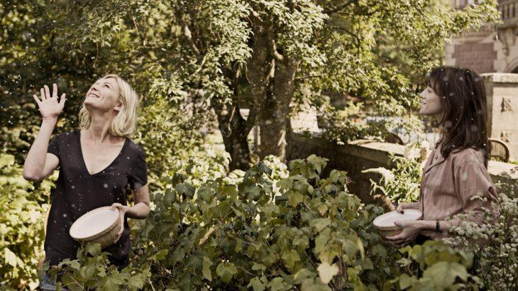 mujer rubia y mujer cabello oscuro en jardin viendo nevar