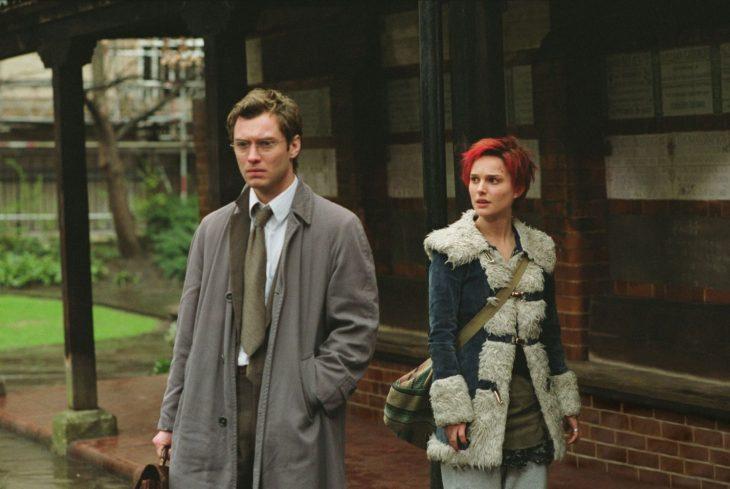hombre de espaldas y mujer de cabello rojo con abrigo