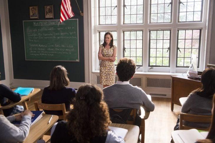 mujer de cabello negro frente a pizarron dando clases