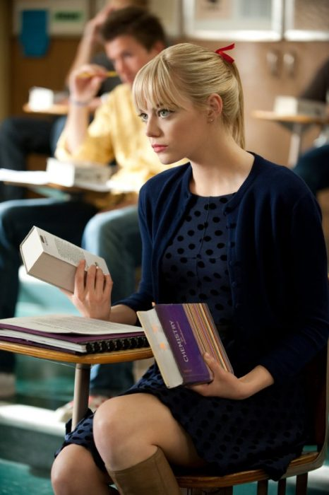 mujer rubia con un libro en la mano sentada en un pupitre