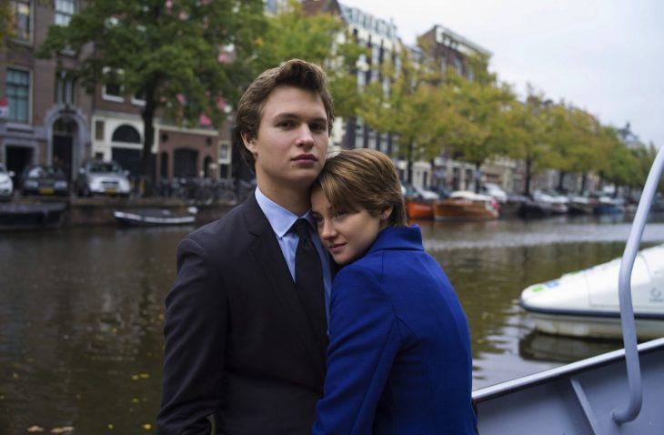 hombre rubio y mujer de cabello corto abrazándolo al lado de un rio