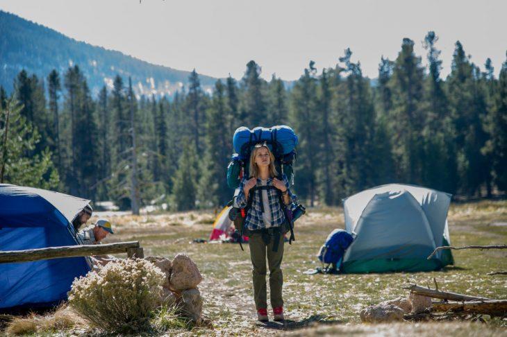 mujer rubia con mochila en el bosque