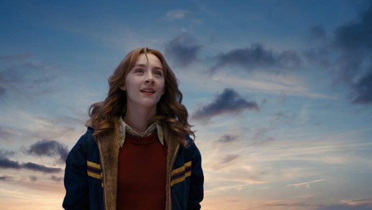 chica rubia de cabello largo y cielo con nubes atrás