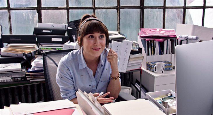 mujer de cabello negro contestando telefono en trabajo
