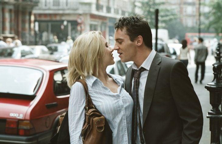 mujer rubia besando a hombre en la calle