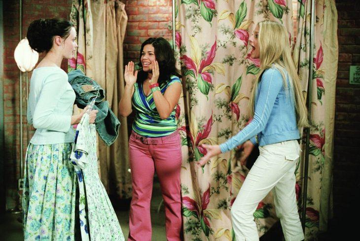 chica de cabello negro y chica rubia hablando y probándose ropa