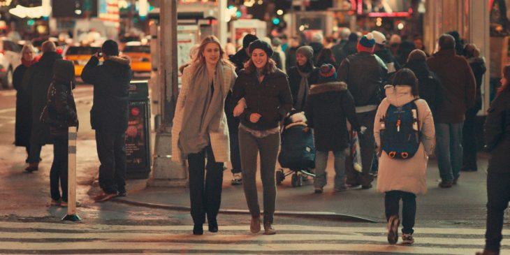 dos mujeres sonriendo cruzando la calle