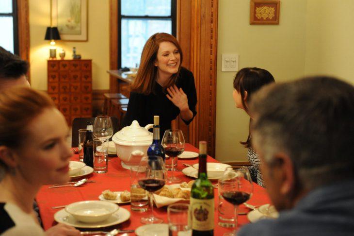 mujer cabello pelirrojo sonriendo en una mesa con copas de vino