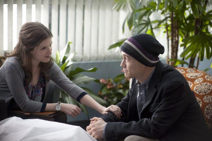 mujer sentada pone su mano en brazo de hombre con gorra