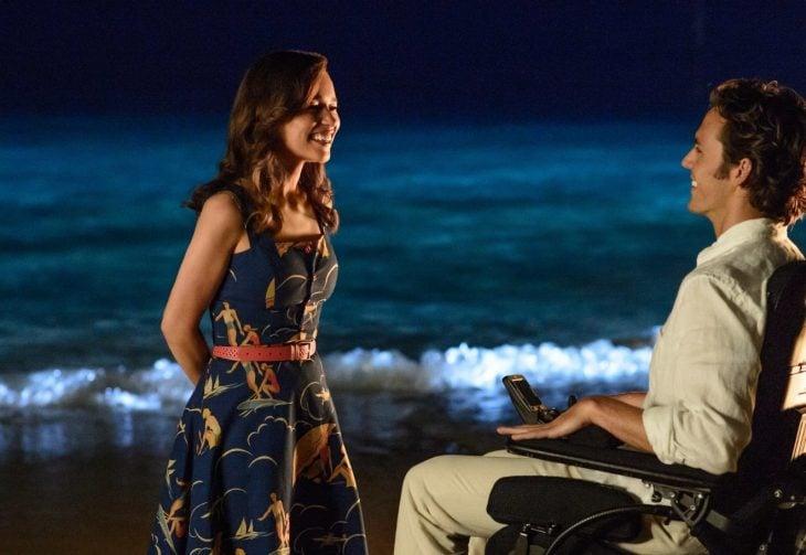 mujer frente a hombre sentado en la playa por la noche