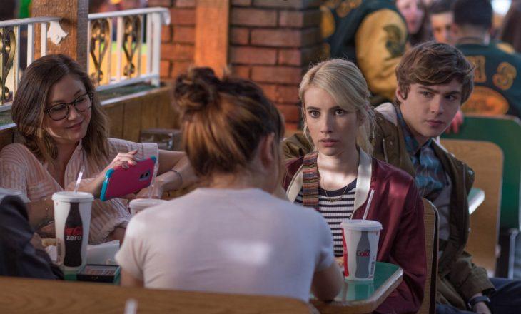 mujer rubia sentada en una mesa con amigos