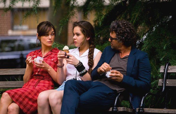 dos mujeres y un hombre sentados en una banca