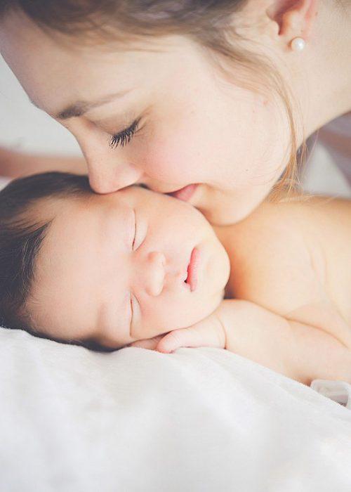 Chica besando el cachete de un bebé