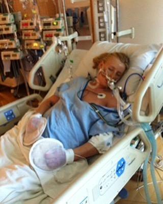 Modelo Lauren Wasser recostada en la cama de un hospital