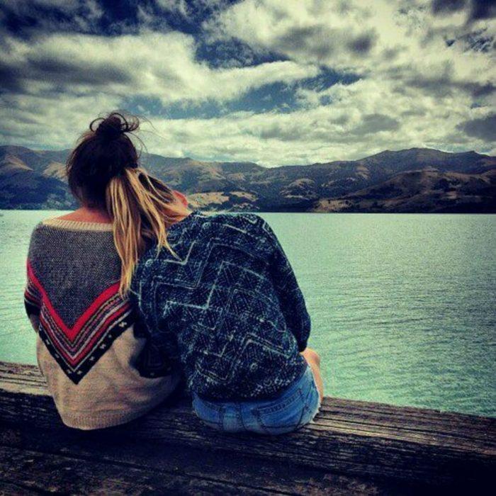 Amigas sentadas en la orilla de un lago