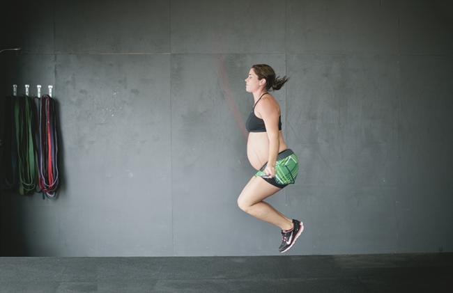 Mujer embrazada saltando la cuerda en un gimnasio