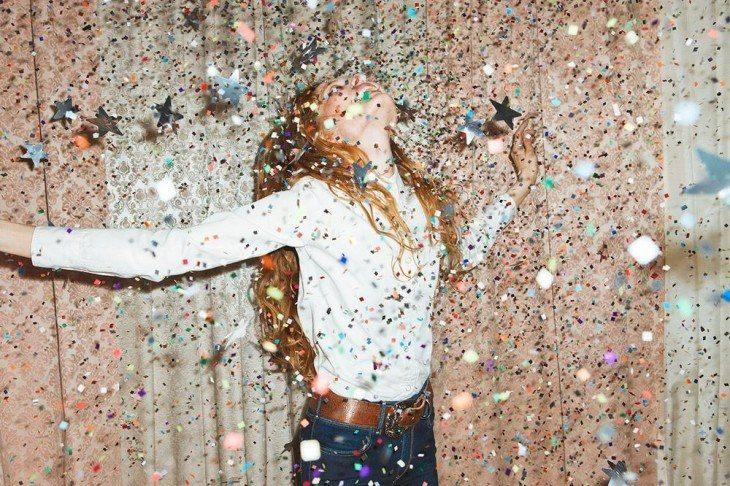 Chica feliz en un cuarto con estrellas de papel