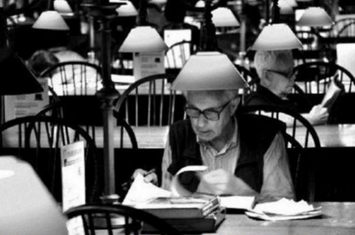 hombre sentado en una mesa leyendo con lampara arriba